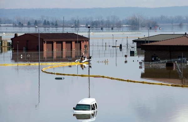 Environmental restoration employees deploy a containment boom from a boat on Offutt Air Force Base in Nebraska. (Delanie Stafford/Air Force via AP)