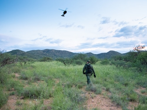 A Border Patrol agent surveys a clearing near Sasabe, Ariz., while a National Guard UH-60 Black Hawk provides air support on Aug. 13, 2018. About 800 active-duty troops are headed to the region to assist with security efforts. (Lu Maheda/Department of Homeland Security)