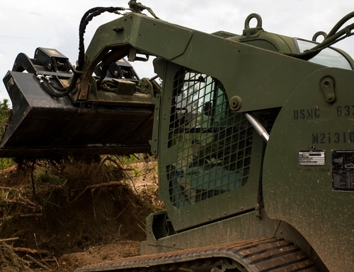 Sergeant Gage Kono, a heavy equipment operator with the Special Purpose Marine Air-Ground Task Force-Southern Command and a Seattle, Wash. native, unloads debris into a consolidated pile cleared from an airfield in Mocoron, Honduras, July 18, 2015. Marines with the SPMAGTF-SC are renovating the airfield as part of a larger mission to create a partnership based on shared values, challenges and responsibilities. (U.S. Marine Corps photo by Sgt. Andy J. Orozco/Released)