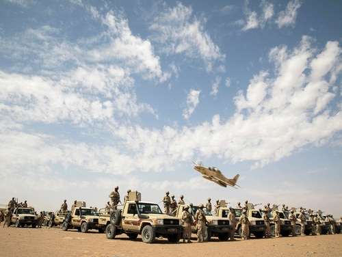 An A-29B Super Tucano flies over Mauritanian Army soldiers as they pose for a picture in Atar, Mauritania, Feb. 17, 2020, during Flintlock 2020, U.S. Africa Command's largest annual special operations forces exercise. (Pfc. Clara Soria-Hernandez/Army)