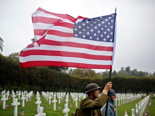 In this Sept. 23, 2018, file photo, re-enactors in World War I military uniforms carry an American flag in the Meuse-Argonne cemetery in northeastern France. (Thibault Camus/AP)