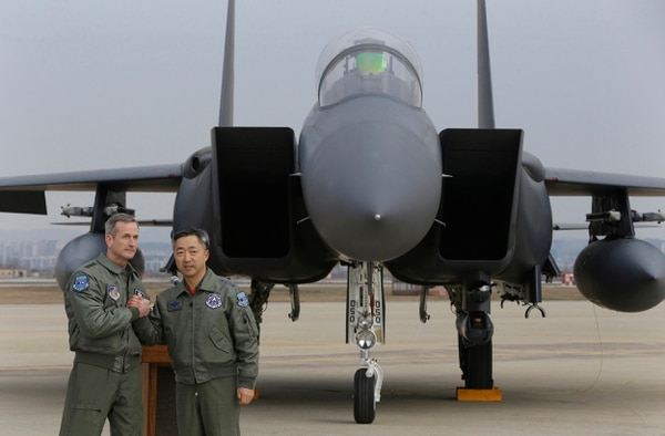Lt. Gen. Terrence O'Shaughnessy, left, 7th Air Force commander of the U.S. Forces to Korea, and South Korean Air Forces Commander Lee Wang-geun pose in front of a South Korean F-15K fighter jet after a press briefing on the flight by a U.S. Air Force B-52 bomber over South Korea at the Osan Air Base in Pyeongtaek, South Korea, Sunday, Jan. 10, 2016. A powerful U.S. B-52 bomber flew low over South Korea on Sunday, a clear show of force from the United States as a Cold War-style standoff deepened between its ally Seoul and North Korea following Pyongyang's fourth nuclear test. The B-52 was joined by South Korean F-15 and U.S. F-16 fighters and returned to its base in Guam after the flight, the U.S. military said. (AP Photo/Ahn Young-joon)