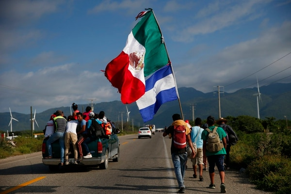 A migrant carrying the flags of Mexico and Honduras walks along the highway as a thousands-strong caravan of Central Americans hoping to reach the U.S. border moves onward from Juchitan, Oaxaca state, Mexico on Thursday. Thousands of migrants resumed their slow trek through southern Mexico on Thursday, after attempts to obtain bus transport to Mexico City failed. (Rebecca Blackwell/AP)