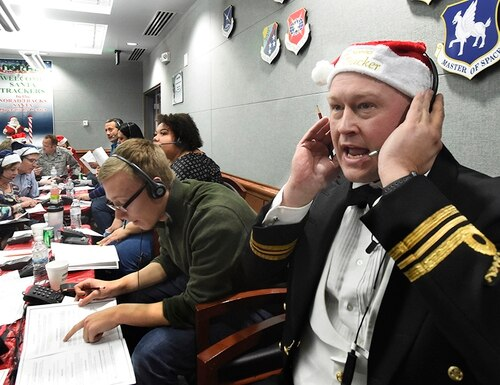 In this Dec. 24, 2017, file photo, Canadian Lt. Maj. Chris Hache takes a call while volunteering at the NORAD Tracks Santa center at Peterson Air Force Base in Colorado Springs, Colo. Hundreds of volunteers will help answer the phones again when the program resumes on Monday, Dec. 24, 2018, for the 63rd year. Children from around the world call to ask when Santa Claus will get to their house. (Jerilee Bennett/The Gazette via AP)