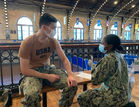 Hospitalman Bianca Lavagesse, right, assigned to Naval Health Clinic Annapolis, administers an influenza vaccination to Midshipman Alexander Krupinsky on Oct. 16, 2020, during an U.S. Naval Academy influenza vaccination exercise. (Lt. Thomas Hurtado/Navy)