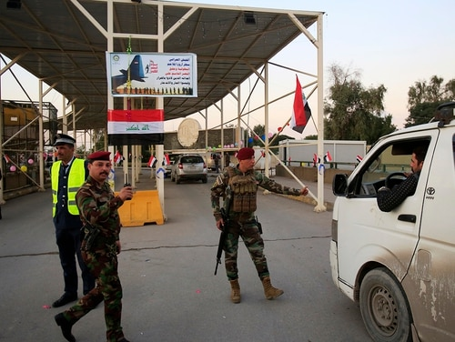 Iraqi security forces stand guard as they check motorists entering the so-called Green Zone in Baghdad, Iraq, on Dec. 10, 2018. Iraq celebrated the anniversary of its costly victory over the Islamic State group, which has lost virtually all the territory it once held but still carries out sporadic attacks. (Karim Kadim/AP)