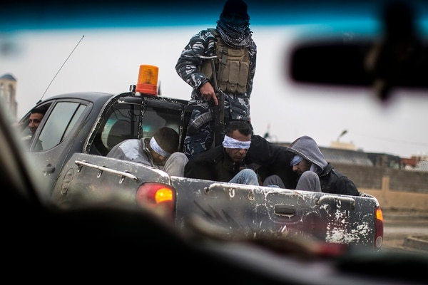 Christian militia fighters from the Nineveh Plain Protection Units drive a pick-up truck in Qaraqosh (also known as Hamdaniya), transporting four men, who are allegedly members of the Islamic State group that were found inside a tunnel in Mosul, on Dec. 20, 2016. (JM Lopez/AFP via Getty Images)