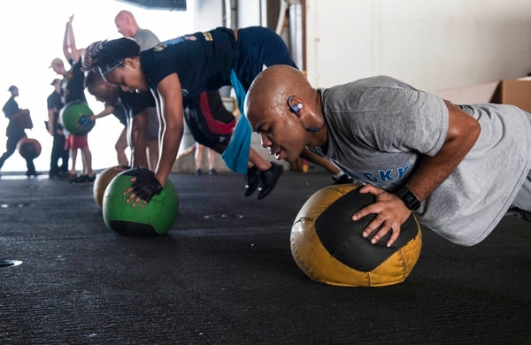 150810-N-GR120-042 ARABIAN GULF (Aug. 10, 2015) Aviation Electrician's Mate 2nd Class Dennis Ross performs burpees with a medicine ball during a functional fitness class in the hangar bay aboard the aircraft carrier USS Theodore Roosevelt (CVN 71). Theodore Roosevelt is deployed in the U.S. 5th Fleet area of operations supporting Operation Inherent Resolve, strike operations in Iraq and Syria as directed, maritime security operations and theater security cooperation efforts in the region. (U.S. Navy photo by Mass Communication Specialist 3rd Class Anna Van Nuys/Released)