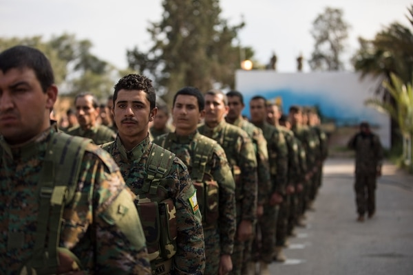 Members of the Syrian Democratic Forces stand in formation during a victory announcement ceremony over the defeat of the Islamic State group's so-called physical caliphate March 23, 2019, at Omar Academy, Deir ez-Zor, Syria. (Staff Sgt. Ray Boyington/Army)