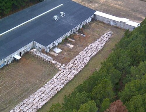 This 2012 aerial photo provided by the Louisiana State Police shows a portion of the M6 artillery propellant improperly stored outside Explo Systems Inc., a munitions dismantling facility at Camp Minden in Minden, La. The National Guard is preparing to start a privately contracted $32 million cleanup to destroy millions of pounds of dangerous materials by burning it over the course of a year. (Louisiana State Police via AP)