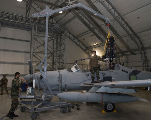 Afghan Air Force A-29 maintainers carefully maneuver an ejection seat on Feb. 14, at Kabul Air Wing, Afghanistan. Before removing ejection seats, AAF maintainers are trained to safely handle the explosives used to jettison the seat when activated. (Staff Sgt. Jared Duhon/Air Force)