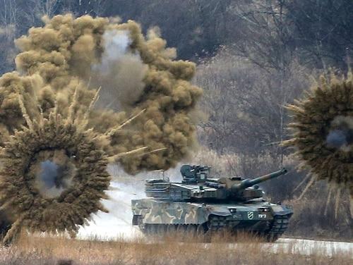 Smoke bombs explode near a South Korean army K-2 tank during a live firing drill at a fire training field in Yangpyeong, South Korea, Thursday, Feb. 18, 2016. (Lim Hun-jung/Yonhap via AP)
