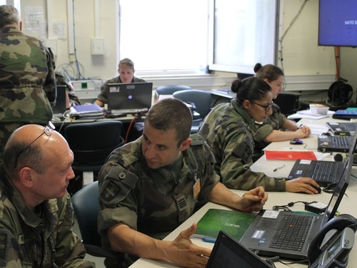 French soldiers comb through information streaming in from both a virtual battlefield and real operational activities at its mission command headquarters at the U.S. Army-hosted Joint Warfighting Assessment at Grafenwoehr, Germany. (Jen Judson/Staff)