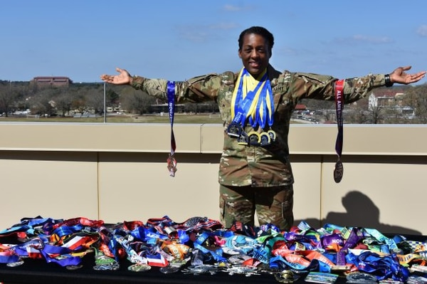 Beofra K. Butler poses with her marathon medals on March 22. Butler has run 99 marathons since starting with the Marine Corps Marathon in 2008. Around her neck are her medals from her five previous Boston Marathons. She will run her 100th race April 15 in Boston. (Eve Meinhardt/FORSCOM)