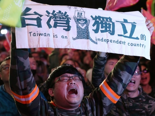 A supporter of Taiwan's presidential election candidate Tsai Ing-wen cheers for her victory and holds a slogan reading