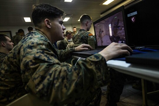 Marine Cpl. Jacob M. Novitski, communicates his location to Marines while participating in simulated squad-level integrated training with Virtual Battlespace Simulator III (VBS III), a computer-generated combat training program, aboard the Wasp-class amphibious assault ship USS Iwo Jima. (Lance Cpl. Tojyea G. Matally/Marine Corps)