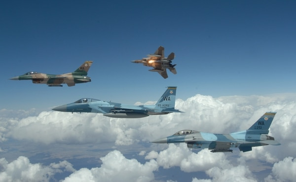 A flight of Aggressor F-15 Eagles and F-16 Fighting Falcons fly in formation over the Nevada Test and Training Ranges. Air Combat Command is contracting out the work of aggressor squadrons so its pilots can focus on the training they need to do. (Master Sgt. Kevin Gruenwald/Air Force)