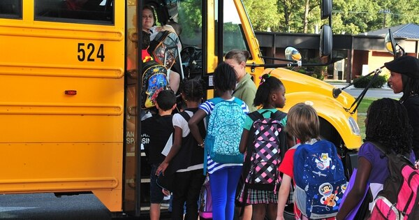 Children of service members assigned to Seymour Johnson Air Force Base, N.C., board a bus for their elementary school. (Air Force)