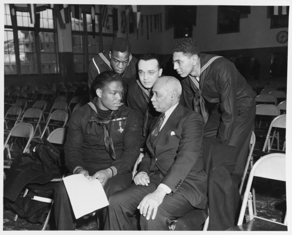 Mess Attendant 1st Class Doris Miller talking with three other sailors and a civilian, during his visit to the Naval Training Station, Great Lakes, Illinois, 7 January 1943. (National Archives)
