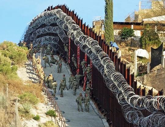 Soldiers place additional concertina wire to the border fence on a hillside above Nelson Street in downtown Nogales, Ariz. (Jonathan Clark/Nogales International via AP)
