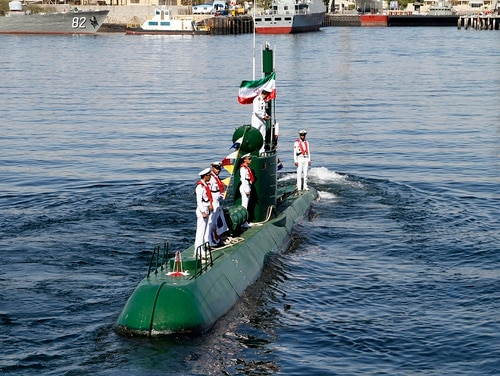 Members of Iran's navy stand on the Ghadir-942 submarine in southern port of Bandar Abbas, Iran, at the mouth of the strategic Strait of Hormuz, Thursday, Nov. 29, 2018. Iran's navy has acquired two new mini submarines designed for operations in shallow waters such as the Persian Gulf, the Iranian state TV reported on Thursday. (Rahbar Emamdadi/Mehr News Agency via AP)