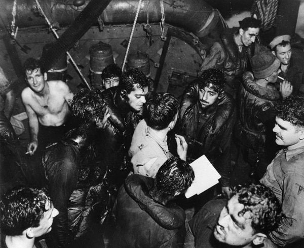 Oil-covered survivors from the USS Helena respond to roll call aboard a Navy destroyer that rescued them. (Naval History and Heritage Command)