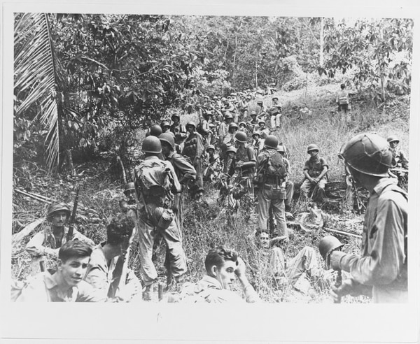 U.S. Marines rest in the field on Guadalcanal, circa August-December 1942. Most of these Marines are armed with M1903 bolt-action rifles and carry M1905 bayonets and USMC 1941 type packs. Two men high on the hill at right wear mortar vests and one in center has a World War I type grenade vest. The Marine seated at far right has a Browning Automatic Rifle. (National Archives)