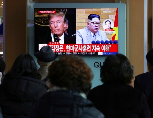 People watch a TV screen showing North Korean leader Kim Jong Un, right, and U.S. President Donald Trump at the Seoul Railway Station in Seoul, South Korea, Friday, March 9, 2018. (Ahn Young-joon/AP)