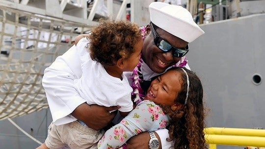 FC1 Kial Hartwell is greeted by his children during the homecoming ceremony for the guided-missile destroyer USS O'Kane (DDG 77) at Joint Base Pearl Harbor-Hickam. O'Kane is returning from an independent deployment to the western Pacific in support of theatre operations. (MCS1 Holly L. Herline/Navy)