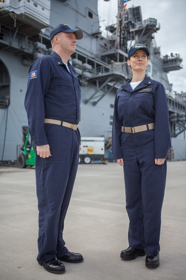 Naval Station Norfolk (Jan 13, 2017 -- The amphibious assault ship Kearsarge stands as the backdrop for Lt. Cmdr. Ken Gilmore (L) and Lt. Cmdr. Heather Flores Fleet Forces Command wearing the approved version of the Improved Fire Retardant Variant Coverall that FFC announced this week. The new coveralls are expected to make their fleet debut in late fall, 2017 and could be adopted into the seabag in the future. Photo by Mark D. Faram/staff