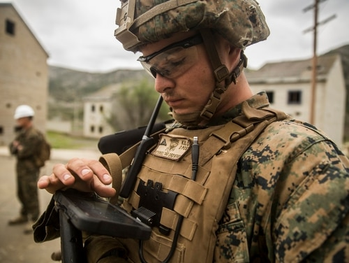 A rifleman with Kilo Company, 3rd Battalion, 4th Marine Regiment, 1st Marine Division, looks at a tablet that has been enhanced with Beartooth radio, test new communication capabilities with a digital radio that pairs with mobile devices to send encrypted short bursts of data via long ranges without reliance on infrastructure, during the Urban Advanced Technologies Exercise 2018. (Lance Cpl. Robert Alejandre/U.S. Marine Corps)