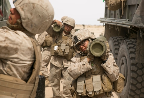 Cpl. Caroline Ortiz, a Marine with the Ground Combat Element Integrated Task Force, carries a shell during an artillery assessment at Marine Corps Air Ground Combat Center Twentynine Palms in Twentynine Palms, Calif., on Friday, April 10, 2015. In addition to artillery, the GCEITF is also evaluating the integration of female Marines into infantry and mechanized MOS's. (Mike Morones/Staff)