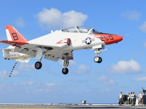 Before the bottle bet ban took effect, a T-45C Goshawk, assigned to Training Air Wing 2, prepares to land on the flight deck of the aircraft carrier Harry S. Truman, which was underway in the Atlantic Ocean for Carrier Qualifications. (Navy)