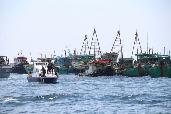 An Indonesian Maritime and Fisheries Ministry patrol boat sails past foreign fishing boats caught operating illegally in Indonesian waters before sinking them off Datuk Island, West Kalimantan, Indonesia, on Saturday. (William Pasaribu/AP)