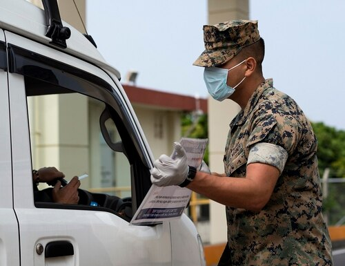 U.S. Marines part of the Security Augmentation Force conduct health and wellness checks of pool individuals entering Camp Foster in an effort to combat the spread of COVID-19, on Camp Foster, Okinawa, April 3. (Cpl. Kameron Herndon/Marine Corps)