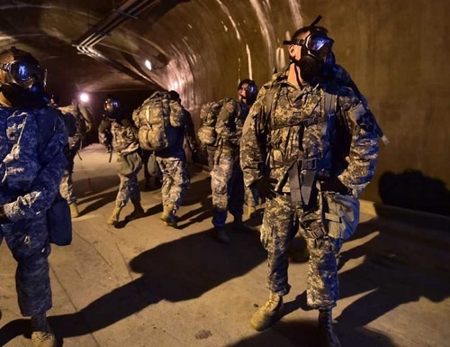 Soldiers wearing gas masks move through a tunnel during a competition to test individual skills at Uijeongbu, South Korea. The Army is seeking a portable device for soldiers to map remote tunnels so they can anticipate what's ahead in the dark. (Jung Yeon-Je/AFP/Getty Images)
