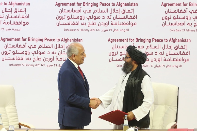 U.S. peace envoy Zalmay Khalilzad, left, and Mullah Abdul Ghani Baradar, the Taliban group's top political leader shack hands after signing a peace agreement between Taliban and U.S. officials in Doha, Qatar, Saturday, Feb. 29, 2020. (Hussein Sayed/AP)