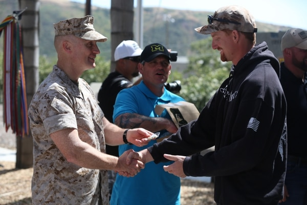 "MARINE CORPS BASE CAMP PENDLETON, Calif. – Cpl. Ryan Provasi accepts a challenge coin from Col. Jason Morris at the 3rd Battalion, 5th Marine Regiment ""Dark Horse"" Reunion at the San Mateo Memorial Garden April 29, 2016. Provasi served as a rifleman with Company K during the battalion's deployment to Sangin, Afghanistan in the fall of 2010. (U.S. Marine Corps photo by Lance Cpl. Shellie Hall/Released)"