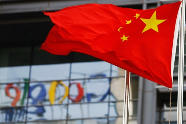 The Google logo is reflected in windows of the company's China head office as the Chinese national flag flies in the wind in Beijing on March 23, 2010. (li xin/AFP via Getty Images)