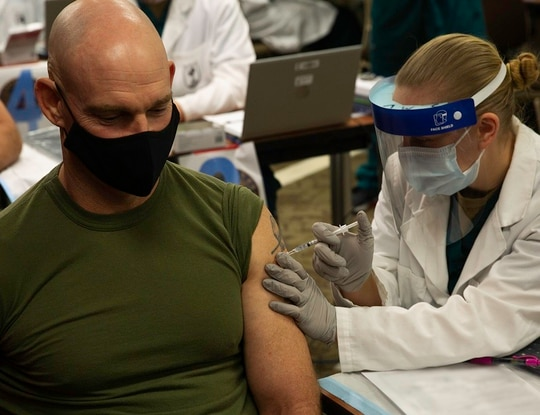 Sergeant Major of the Marine Corps Sgt. Maj. Troy E. Black receives the COVID-19 vaccine as part of Operation Warp Speed at Walter Reed National Military Medical Center, Maryland, Dec. 22, 2020. (Lance Cpl. Tyler W. Abbott/Marine Corps) (This photo has been altered for security purposes by blurring out medical documentation.)