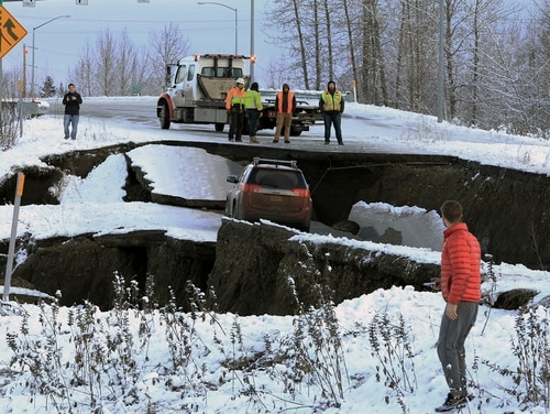 Highway workers and spectators look at a car stuck on a section of an off-ramp that collapsed during an earthquake Friday morning in Anchorage, Alaska. The driver was not injured attempting to exit Minnesota Drive at International Airport Road. (Dan Joling/AP)