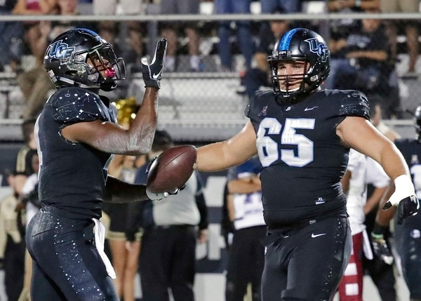 Central Florida running back Taj McGowan, left, celebrates with offensive lineman Cole Schneider after scoring a touchdown on a 1-yard run against Temple on Nov. 1 in Orlando. (John Raoux/AP)