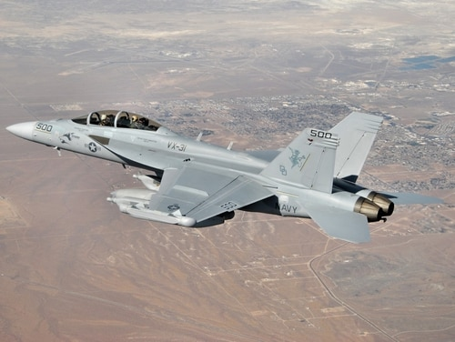 "A Navy Boeing EA-18G Growler of test and evaluation squadron VX-31 flies over the city of Ridgecrest, California, as it returns to NAWS China Lake at the conclusion of a test mission on the Electronic Combat Range (Echo). The aerial electronic attack platform is configured with three ALQ-99 jammer pods, which are to be upgraded during a three-increment ""Next-Gen Jammer"" development program. (CMDR Ian C. Anderson/Navy)"