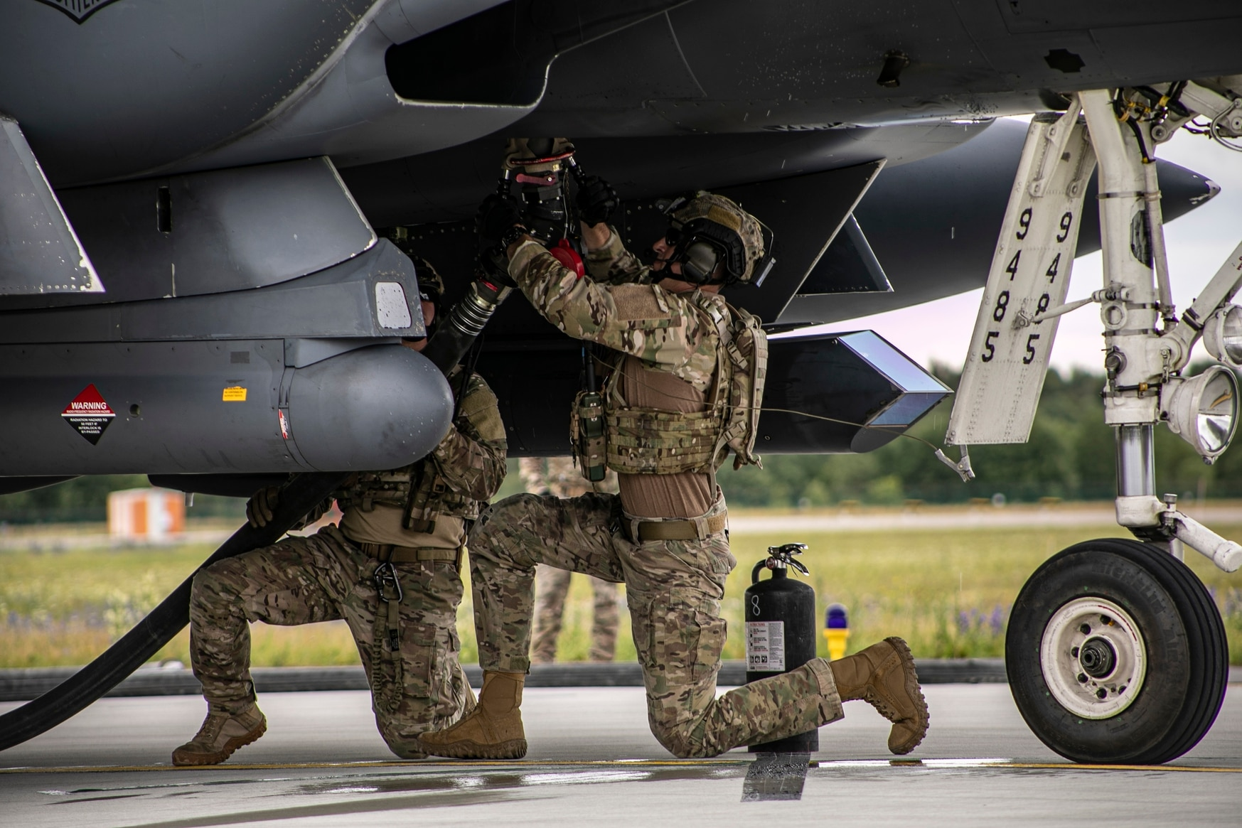 Two U.S. Air Force logistics readiness airmen attach a fuel nozzle underneath an F-15E Strike Eagle during a forward air refueling mission July 16 at Amari Air Base, Estonia. The mission was part of Operation Rapid Forge. (Sgt. Alexis Washburn-Jasinski/U.S. Army)
