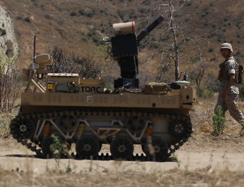 Pfc. Jasper Jauregui, an infantryman with Kilo Company, 3rd Battalion, 5th Regiment, patrols next to the robotic vehicle modular system aboard Camp Pendleton, Calif., June 23, 2016. The system is still in development and will be tested during exercise Rim of the Pacific. The Marine Corps Warfighting Laboratory is conducting a Marine Air-Ground Task Force Integrated Experiment to explore new gear and access its capabilities for potential future use. (U.S. Marine Corps photo by Lance Cpl. Frank Cordoba/Released)