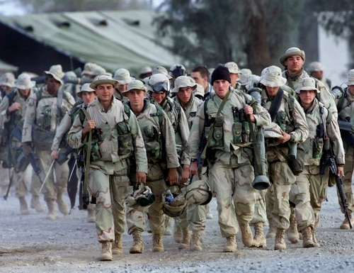 In this Dec. 31, 2001, file photo, U.S. Marines with full battle gear prepare to leave the U.S. military compound at Kandahar airport for a mission to an undisclosed location. (John Moore/AP)