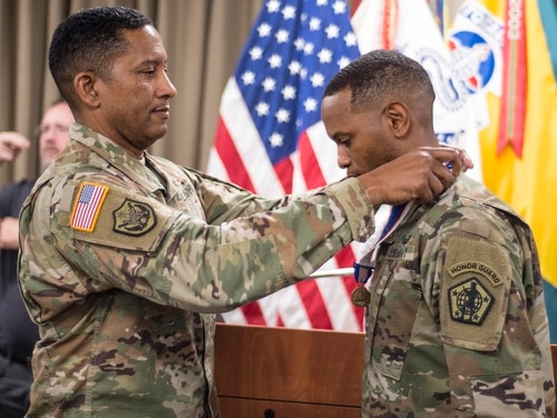 Sgt. 1st Class Mario King, Army Human Resources Command information technology specialist career adviser, is presented the Soldier's Medal during a ceremony hosted by Maj. Gen. Jason Evans, Army Human Resources Command commanding general. (Master Sgt. Brian Hamilton/Army)