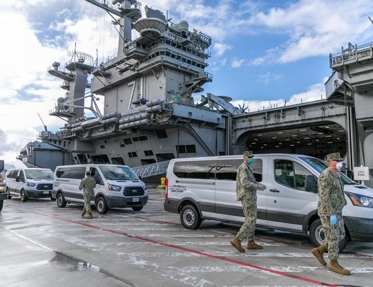 A sailor from the carrier Theodore Roosevelt, seen here portside in Guam, was found unresponsive Thursday morning after testing positive 10 days ago for COVID-19. (MCC Matthew White/Navy)