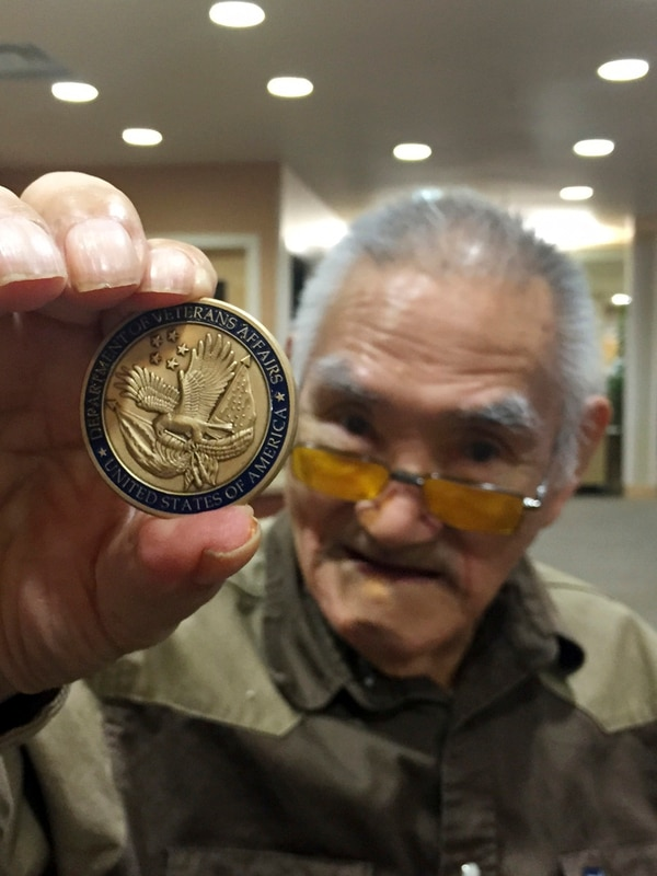 In this photo provided by NANA Regional Corp., Wendell Booth displays a commemorative coin awarded to him by the Secretary of Veterans Affairs Robert McDonald, at a ceremony Wednesday, Aug. 12, 2015, in Kotzebue, Alaska. McDonald addressed seven surviving members of the largely Native citizens militia during the ceremony. (Luke Magnusson/NANA Regional Corp. via AP)