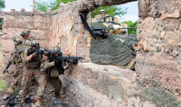 U.S. soldiers assigned to 1st Armored Brigade Combat Team, 1st Cavalry Division check fields of fire as an M2A3 Bradley fighting vehicle provides support at Vaziani Training Area, Georgia, Aug. 4, 2018.